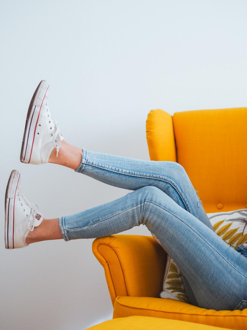 woman in blue denim jeans and white converse all star high top sneakers sitting on orange